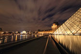 PARIS - January 8th 2012 : Closeup of Louvre Pyramid shined at dusk in Paris, France. — Stock Photo
