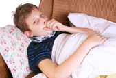 Young ill child coughing in bed — Stock Photo