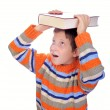 Student child with a book on his head — Stock Photo