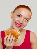 Smiling woman with hamburger — Stock Photo