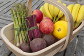 Mixed bunch of fresh vegetables and fruit produce in basket outd — Stock Photo