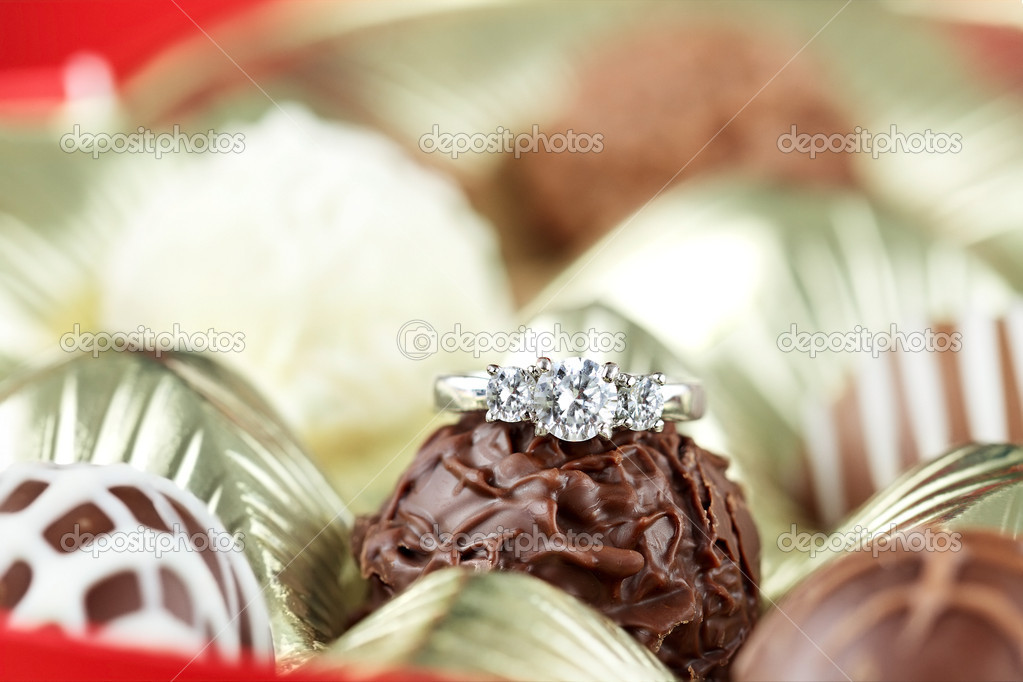 Diamond engagement inside of a box of chocolate truffles. Extreme shallow depth of field with selective focus on diamond ring. — Stock Photo #8414732