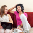 Two happy beautiful girls listening to music from the notebook and through headphones — Stock Photo