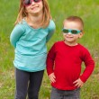 Brother and sister posing outside with sunglasses on their eyes on beautiful spring day — Stock Photo