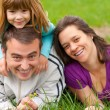 Young happy family having fun in the grass on beautiful spring day — Stock Photo #10130654