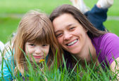 Mother and daughter having fun in the grass on beautiful spring day — Stock Photo