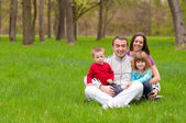 Young happy family having fun in the nature on beautiful spring day — Stock Photo