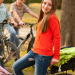Cute happy teenage girl riding bicycles with her friends — Stock Photo