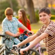 Happy teenage boy spending time with his friends riding bicycles — Stock Photo #10365449