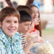 Handsome chubby teenager spending time with his friends outdoor — Stock Photo