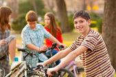 Felice ragazzo adolescente trascorrere del tempo con i suoi amici in sella a biciclette — Foto Stock