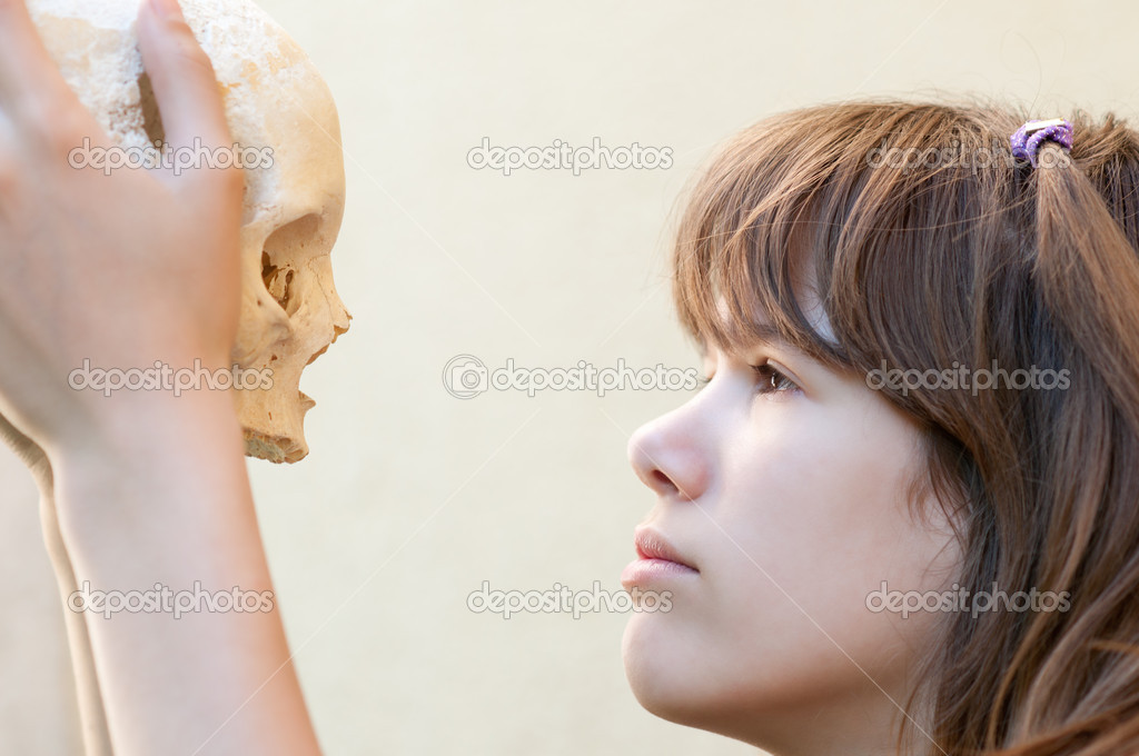 Teenage girl looking at human skull and thinking about life and death — Stock Photo #10396984