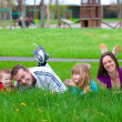 Young happy family having fun in the grass on beautiful spring day — Stock Photo