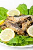 Smelt with lemon slices and green salad isolated on white — Stock Photo
