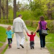 Young family walking in the park on cloudy spring day — Stock Photo
