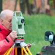 Land surveyor measuring with total station on construction site - Stock Photo