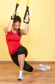 Beautiful young girl exercising in the gym with suspension device — Stock Photo