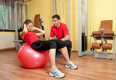 Beautiful young girl exercising abs in the gym under supervision of her coach — Stock Photo
