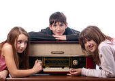 Three teenage friends listening to music on the old radio isolated on white — Stock Photo