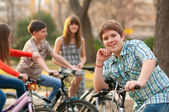 Happy teenage boy spending time with his friends riding bicycles — Stock Photo