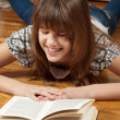 Happy teenage girl reading a book on the wooden floor — Photo