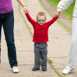 Little boy holding hands of his parents while walking in the park. — Stock Photo #10728170