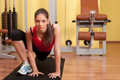 Beautiful young woman exercising in the gym on the floor — Stock Photo