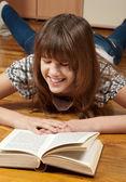 Glad tonårsflicka läser en bok på trägolv — Stockfoto