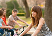 Beautiful teenage girl spending time with her friends riding bicycles — Stock Photo