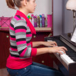 Pretty teenage girl playing on piano in her room — Stock Photo
