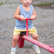 Stock Photo: Smiling boy sitting on teeter on playground on cloudy summer day