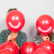 Teenage girls hiding their faces behind smiling balloons — Stock Photo #8116456