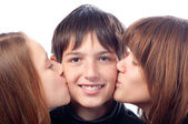 Two pretty girls kissing smiling boy in the cheeks — Stock Photo