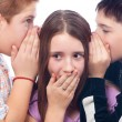 Two cute teenage boys gossiping with teenage girl isolated — Stock Photo #8174109