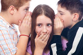 Two cute teenage boys gossiping with teenage girl isolated — Stock Photo