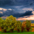 Landscape painting showing trees on the meadow before the storm - Stock Photo