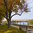 Beautiful autumn day on the sidewalk beside the river - Stock Photo
