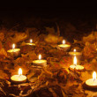 Candle flames lighting the bed of dry leaves on beautiful autumn night — Stock Photo
