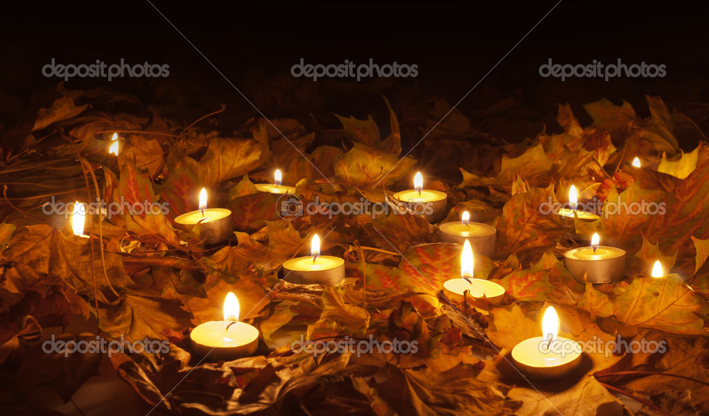 Candle flames lighting the bed of dry leaves on beautiful autumn night — Stock Photo #8410359