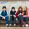 Group of happy teenagers sitting on the street in roller skates on cloudy a — ストック写真