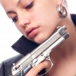 Beautiful girl in black leather jacket and beretta gun in her hands - Foto Stock