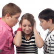 Two angry teenage boys harassing frightened girl - Stock Photo