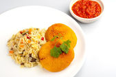 Breaded fried chicken steaks with cooked rice and paprika salad — Stock Photo