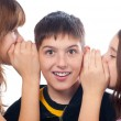 Two girls and a boy gossiping - Stock Photo