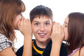 Two girls and a boy gossiping — Stock Photo