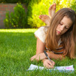 Cute teenage girl lies on the grass and draws in her notebook — Stock Photo