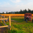 Agriculture landscape showing land, wooden fence and small tractor — Stock Photo
