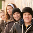 Group of smiling teenage friends posing outside — Stock Photo