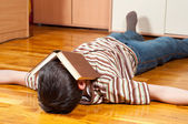 Teenage boy fell asleep while reading on the floor — Stock Photo
