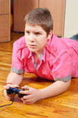 Chubby teenage boy playing computer games using game controller — Stock Photo